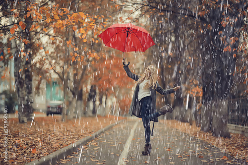 Foto auf Leinwand Lineale Wachstum October walk in the rain, a young woman with a red umbrella in the autumn city park, autumn look