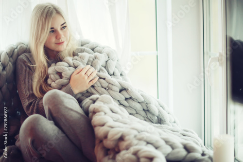 Deurstickers Ontspanning home coziness girl plaid window, home autumn look, model in a warm knitted blanket heats up