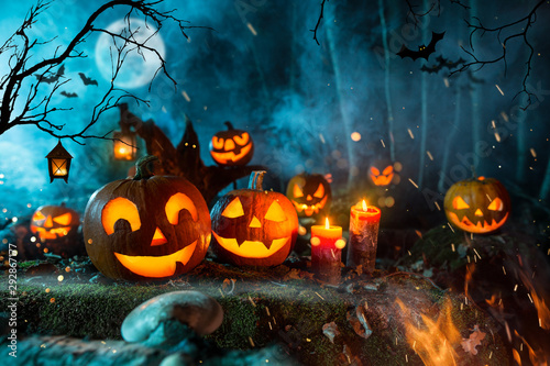 Obraz na plátně Halloween pumpkins on dark spooky forest with blue fog in background