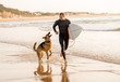 Surfer man with his dog german shepherd and surfboard playing and surfing on the beach
