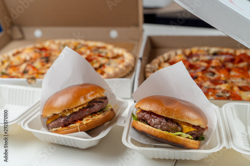 Unhealthy snacks delivery in boxes: italian margherita and chicken pizza, beef burgers with cheddar cheese © Tkachenko Alexey