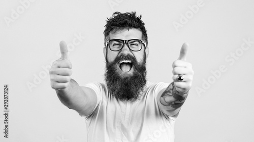 Lucky bearded hipster man over white background. Bearded man wearing glasses. Happy winner. Handsome bearded guy gesturing winner and keeping mouth open. Emotion and gesturing concept.
