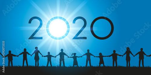 Un groupe d'hommes et de femmes de tous les âges ainsi que des enfants qui se donnent la main face au soleil et à l'année 2020 qui s'inscrit dans le ciel Wallpaper Mural