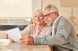 canvas print picture - Senioren Paar liest zusammen einen Vorsorge Plan