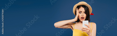 panoramic shot of shocked pretty girl in straw hat using smartphone isolated on Wallpaper Mural