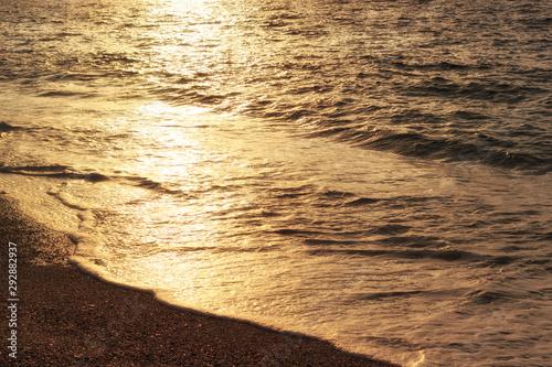 Foto auf Leinwand Dunkelbraun Sunset reflection on sea waves. Golden sunlight on waves of coastline. Sea beach at evening, summer vacation.