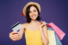 Smiling Girl In Straw Hat With Shopping Bags Showing Credit Card Isolated On Purple