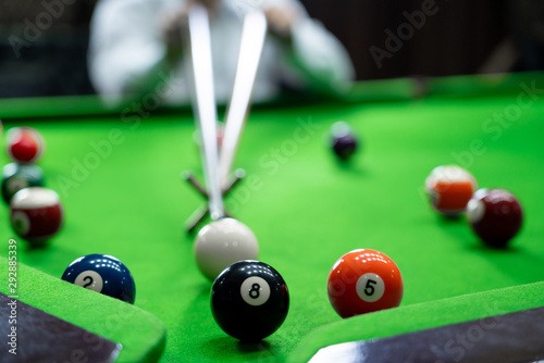Fototapeta  Man's hand and Cue arm playing snooker game or preparing aiming to shoot pool balls on a green billiard table
