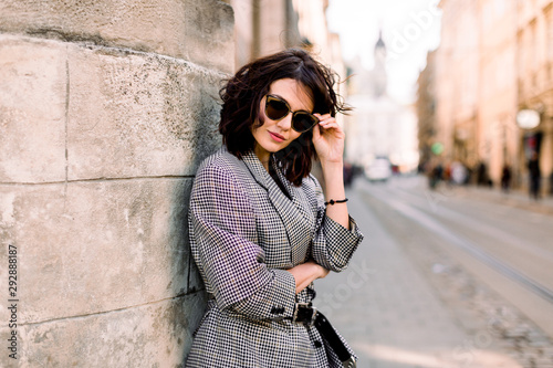 obraz dibond Attractive fashion modern woman in sunglasses standing on the city street. Summer portrait of happy girl on a walk