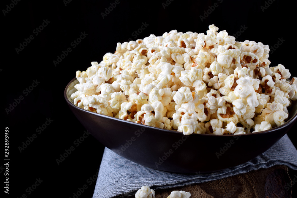 Fototapety, obrazy: Popcorn in a black ceramic bowl on a wooden table against dark background