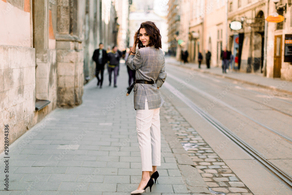 Fototapety, obrazy: Attractive modern woman standing on the city street. Young beautiful girl in stylish elegant clothes walking at sunset along the streets of the city.