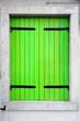 Leinwanddruck Bild - Green window shutters closed on a colorful wall in Burano near Venice, Italy