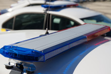 Police Lights. Blue And Red Sirens On The Roof Of Police Car While Policemen Patrol The City