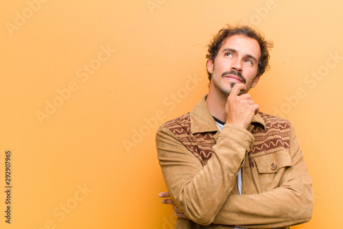 young handsome man feeling thoughtful, wondering or imagining ideas, daydreaming Wallpaper Mural