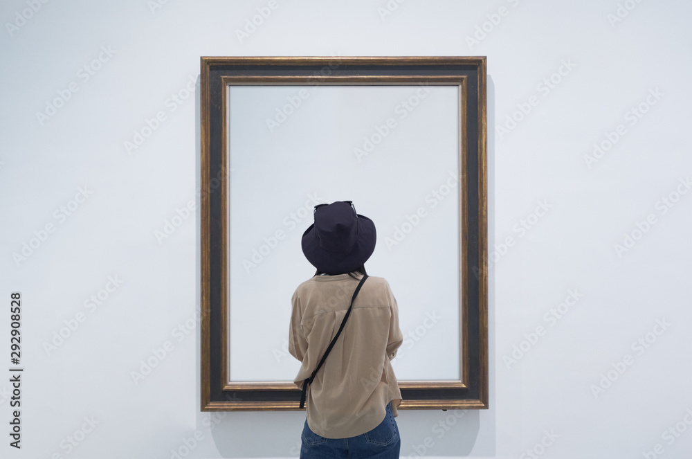 Fototapeta interior view of a lonely girl or tourist looking at blank canvas at a museum or gallery.