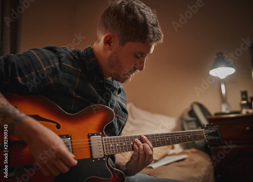 Close-up of a young man practicing playing guitar at evening in his home - 292909343
