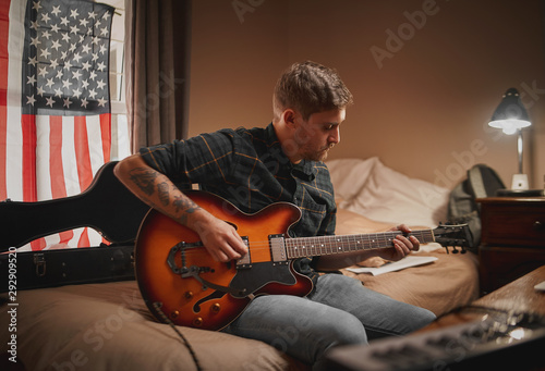 Concentrated young man in casual wear sitting on bed playing guitar at evening - 292909520