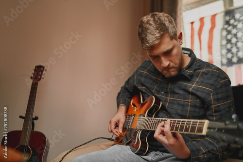 Close-up of a young musician in spare time practices playing guitar at home - 292909738