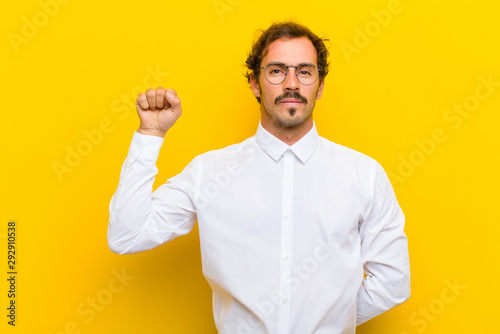 young handsome man feeling serious, strong and rebellious, raising fist up, prot Canvas-taulu