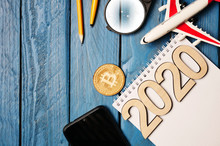 2020 And Notebook With Pen, Wooden Bitcoin, Smartphone And Model Of A Toy Airplane On A Blue Wooden Tabletop, Place For Text.