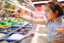 Little Girl Buying Organic Veg...