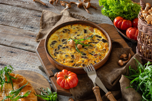 Photo fritata or quiche with agaric mushrooms and cheese inceramic baking dish