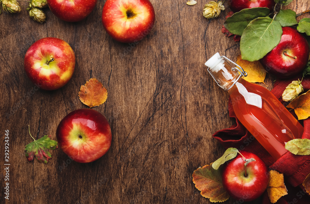 Fototapety, obrazy: Apple cider vinegar. Bottle of fresh apple organic vinegar on wooden table background with cinnamon sticks, anise star, nuts and fallen leaves. Healthy organic food. Copy space
