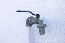 Water Tap On A White Wall Background