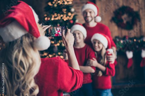 Fototapeta Blurry photo of mom making photo of two children and dad near decorated garland newyear tree indoors family x-mas atmosphere wear santa caps and red sweaters obraz
