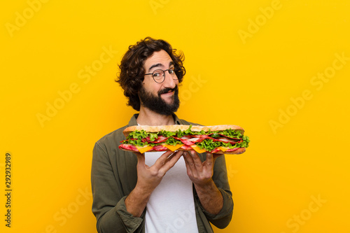 Foto op Plexiglas Snack young crazy bearded man with a giant sandwich.