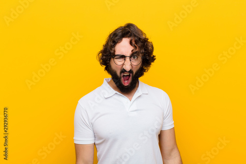 young crazy man looking shocked, angry, annoyed or disappointed, open mouthed an Wallpaper Mural