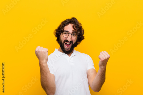 Fotografiet young crazy man feeling happy, surprised and proud, shouting and celebrating suc