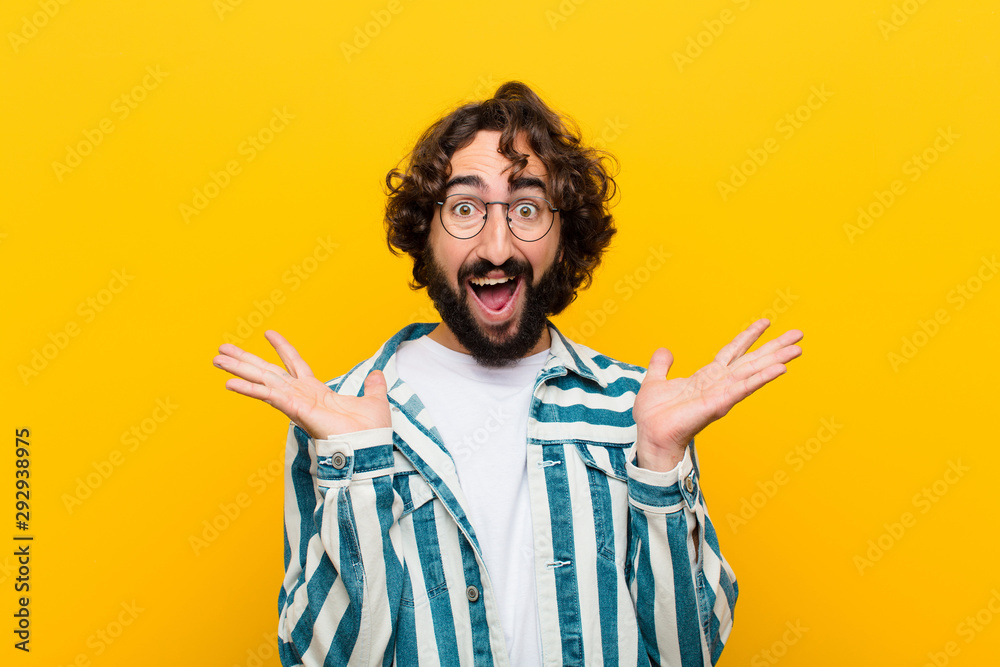 Fototapety, obrazy: young crazy man looking happy and excited, shocked with an unexpected surprise with both hands open next to face against yellow wall