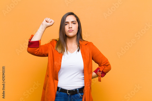 Valokuva young pretty woman feeling serious, strong and rebellious, raising fist up, prot