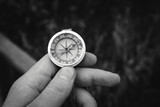 Man hand holding a old compass with broken glass. Travel concept, path selection, navigation, tourism, hiking. Autumn background. crack on the glass as disappointment. black and white