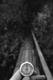 Man hand holding a old compass with broken glass. Travel concept, path selection, navigation, tourism, hiking. Autumn background. crack on the glass wooden bridge. vertical photo, black and white