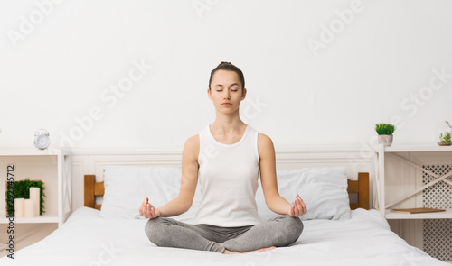 Canvas Prints Equestrian Young sporty woman practicing yoga after waking up