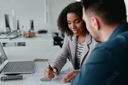 Fototapeta Close-up of young female executive discussing business plan to her colleague with graph and chart on desk obraz