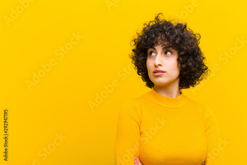 Fotografie, Obraz  young pretty afro woman feeling happy, proud and hopeful, wondering or thinking,