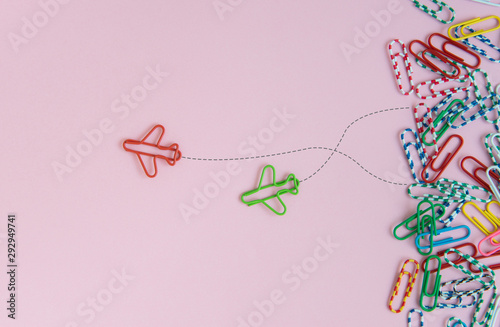 Obraz Business concept for group of stacked paperclip with another two red and green plane paperclip is point to another direction as a team leadership - fototapety do salonu