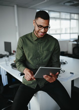 Young Businessman Wearing Eyeglasses Sitting On The Edge Of Office Desk Looking At Digital Tablet