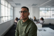 Portrait Of A Serious Young Professional Businessman Wearing Eyeglasses Looking At Camera While Colleague At Background