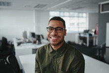 Friendly And Smiling Young African American Professional Businessman Looking At Camera In Modern Office