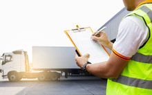 Road Freight Industry Logistics And Transportation, Cargo Shipment, Worker Holding Clipboard His Control Loading Shipment Goods, Trucks Trailer Docking At Warehouse.