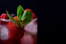 Red Drink With Ice, Raspberries And Mint In A Tall Glass Against The Black Background