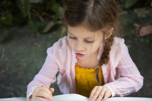 A Little Girl Reading A Story From A Book Outside