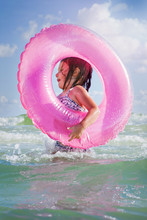 Girl Playing In Waves With Pink Beach Float