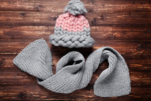 Knitted Hat And Scarf On Brown Wooden Table