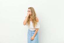 Young Blonde Woman Feeling Disgusted, Holding Nose To Avoid Smelling A Foul And Unpleasant Stench Against White Wall