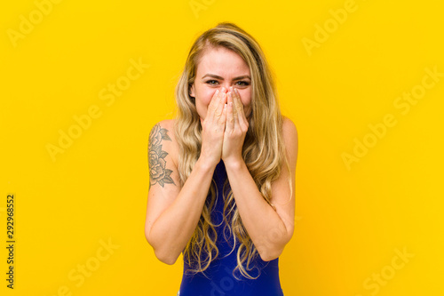Fotografie, Obraz  young blonde woman looking happy, cheerful, lucky and surprised covering mouth w